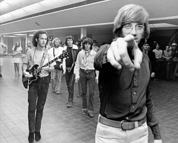 07/10/1968 - the Doors' Ray Manzarek points his finger in the Sam Houston Coliseum lobby. Walking behind him are band members Robby Krieger (with guitar), Jim Morrison (wearing jacket) and John Densmore. The rock band played to a fullhouse in the Coliseum Wednesday night.